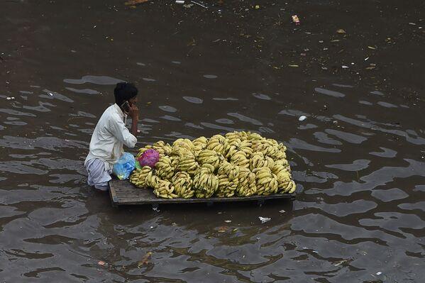 Người bán trái cây với chiếc xe đẩy trên đường phố ngập lụt sau trận mưa lớn ở Lahore, Pakistan - Sputnik Việt Nam