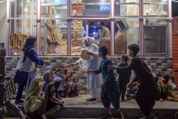 Người phụ nữ phân phát bánh mì cho trẻ em nghèo trước tiệm bánh ở Kabul - Sputnik Việt Nam
