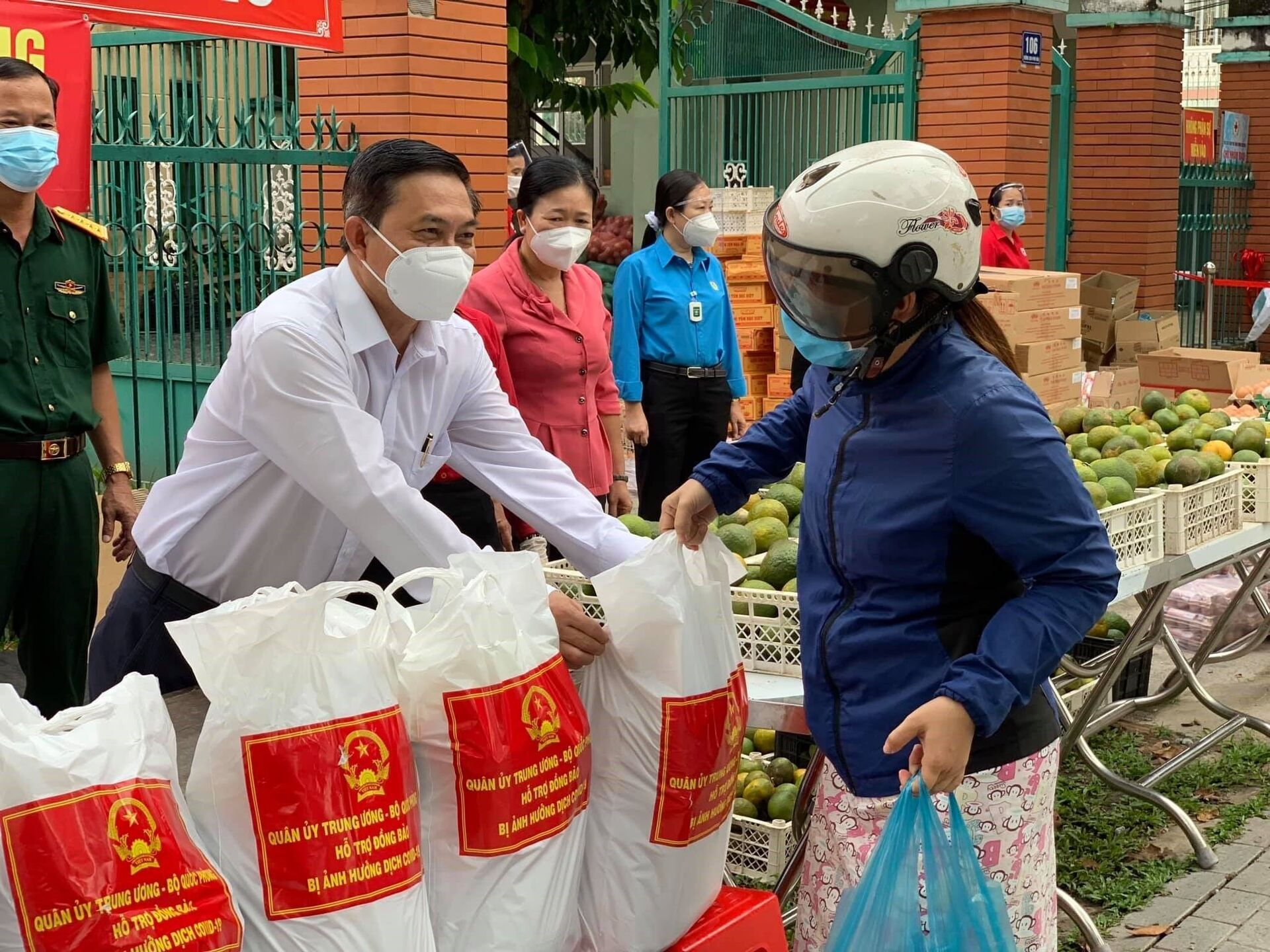 Chủ tịch Mặt trận Tổ quốc Việt Nam tỉnh Bình Dương Nguyễn Văn Lộc (mặc áo trắng) trao túi gạo cho người lao động tại Phiên chợ 0 đồng - Sputnik Việt Nam, 1920, 05.10.2021
