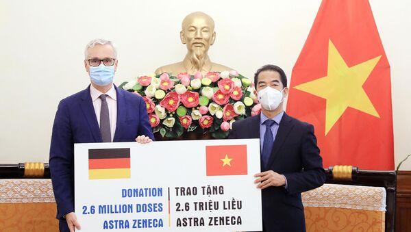 Thứ trưởng Ngoại giao Tô Anh Dũng tiếp nhận tượng trưng 2,6 triệu liều vaccine AstraZeneca từ Đại sứ Đức tại Việt Nam Guido Hildner. - Sputnik Việt Nam