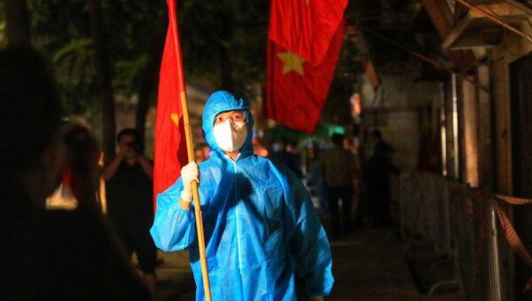 Lực lượng tình nguyện viên cắm cờ tổ quốc trước các nhà trên đường Nguyễn Trãi sau khi có quyết định dỡ bỏ phong tỏa ngõ 328, 330 đường Nguyễn Trãi. - Sputnik Việt Nam