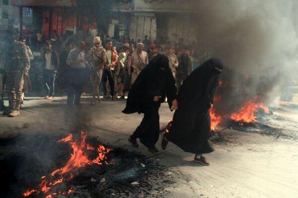 Những người phụ nữ chạy qua đám lốp xe đang cháy trong cuộc biểu tình ở Taiz, Yemen - Sputnik Việt Nam