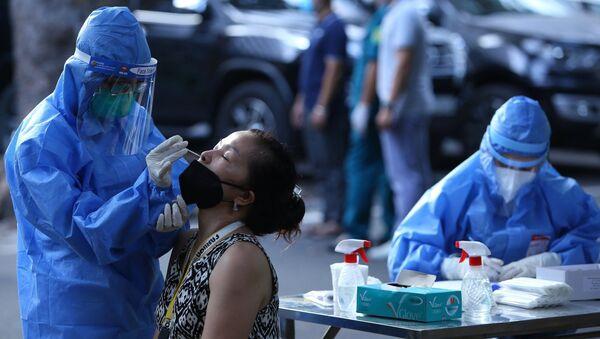 Nhân viên y tế phường Hàng Trống(Hoàn Kiếm) lấy mẫu xét nghiệm cho người dân khu vực lân cận Bệnh viện Việt - Đức. - Sputnik Việt Nam