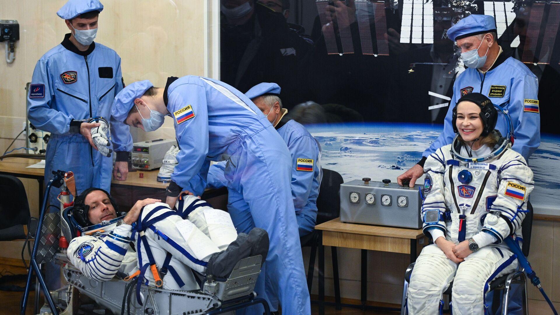 Nữ diễn viên Yulia Peresild và đạo diễn Klim Shipenko mặc bộ đồ vũ trụ trước khi phóng tàu vũ trụ Soyuz MS-19 tại sân bay vũ trụ Baikonur - Sputnik Việt Nam, 1920, 05.10.2021