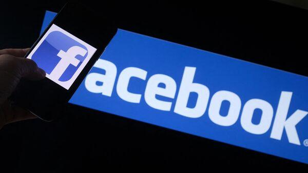 Логотип Facebook на смартфоне перед экраном компьютера в Лос-Анджелесе  - Sputnik Việt Nam