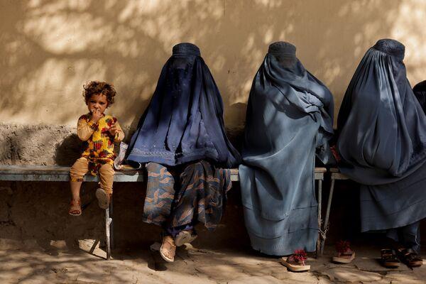 Cô bé bên cạnh những người phụ nữ trong quán rượu bên ngoài bệnh viện ở Kabul - Sputnik Việt Nam