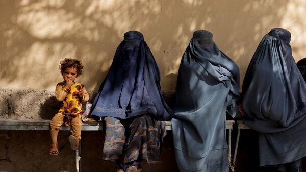 Девочка рядом с женщинами в бурке у больницы в Кабуле  - Sputnik Việt Nam