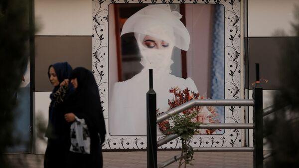 Женщины напротив перерисованного рисунка девушки на стене в Кабуле  - Sputnik Việt Nam