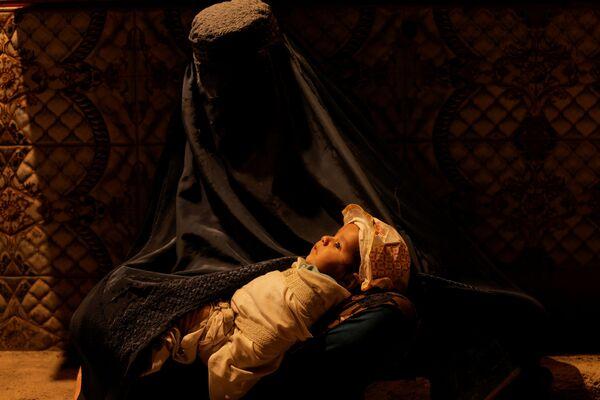 Người phụ nữ mặc áo choàng burqa bế con bên tiệm bánh ở Kabul - Sputnik Việt Nam