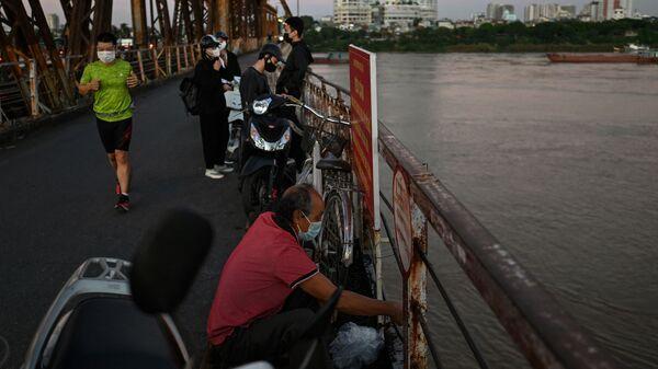 Мужчина ловит рыбу в Красной реке у моста Лонг Бьен в Ханое - Sputnik Việt Nam