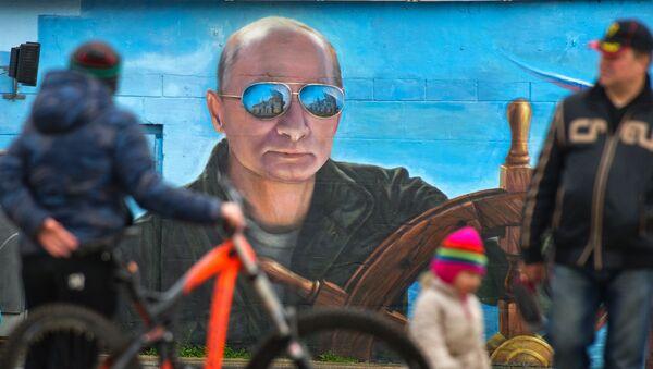 Người đi bộ trước chân dung Tổng thống Nga Putin trên tường một tòa nhà ở Yalta, Crưm. - Sputnik Việt Nam
