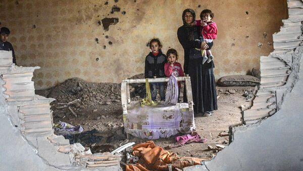 Người phụ nữ cùng đứa con trong ngôi nhà bị phá hủy, Silopi, Thổ Nhĩ Kỳ. - Sputnik Việt Nam