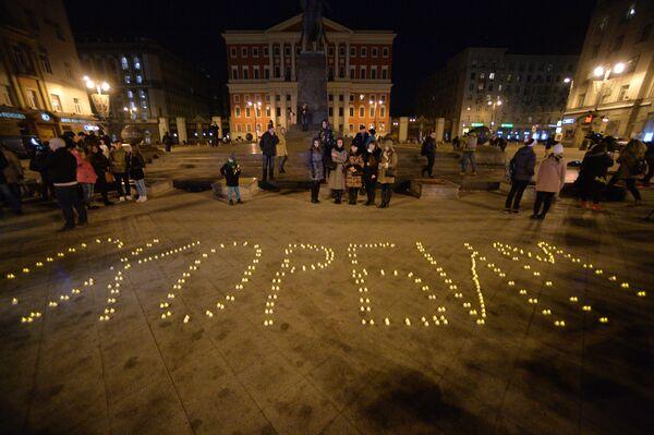 Người dân địa phương đến tượng đài Yury Dolgoruky trước tòa Thị chính Moskva thắp nến đặt hoa tưởng niệm những người thiệt mạng trong vụ tai nạn máy bay Boeing-737 ở Rostov-na-Donu - Sputnik Việt Nam