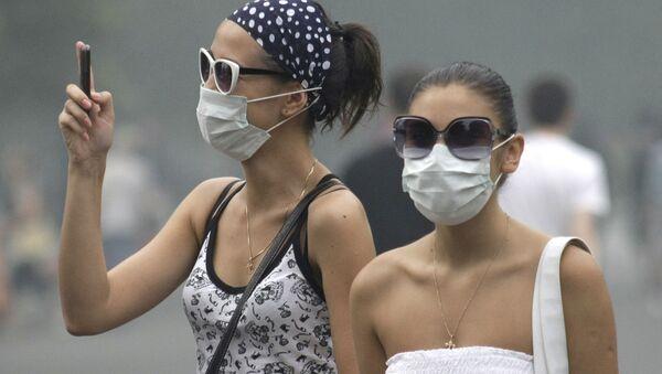 Các cô gái đeo khẩu trang chụp ảnh trên điện thoại - Sputnik Việt Nam