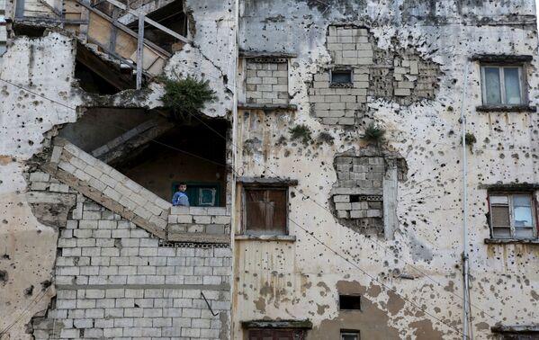 Cậu bé đứng trên cầu thang tòa nhà bị phá hủy ở Lebanon - Sputnik Việt Nam
