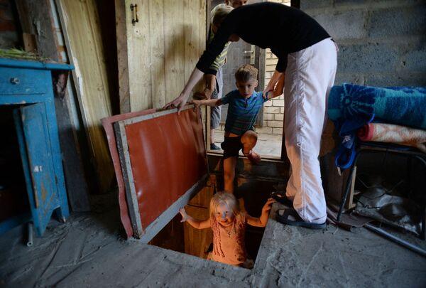 Một gia đình xuống hầm tránh bom trong ngôi nhà ở Kramatorsk, tỉnh Donetsk. - Sputnik Việt Nam