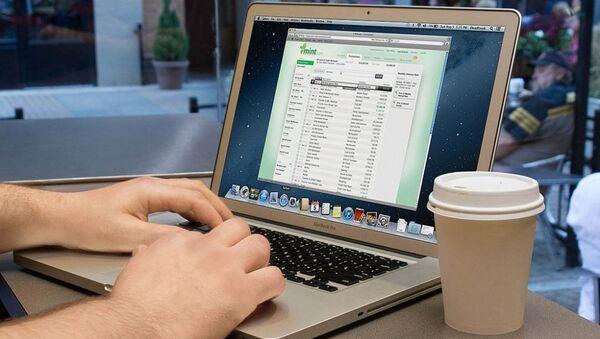 Một người đàn ông làm việc trên laptop trong quán cà phê - Sputnik Việt Nam