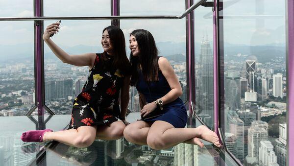 Cô gái Malaysia chụp ảnh trong Sky Box trên nền toàn cảnh từ  tháp truyền hình Kuala Lumpur - Sputnik Việt Nam