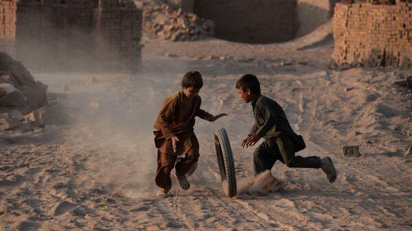 Các trẻ em Afghanistan chơi với bánh xe trên con đường cát bụi ở ngoại ô Jalalabad - Sputnik Việt Nam