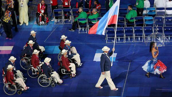Người mang quốc kỳ của đội tuyển Paralympic Nga Alexey Ashapatov (bên phải) tại lễ khai mạc Paralympic mùa hè ХIV trên sân vận động Olympic ở London. - Sputnik Việt Nam