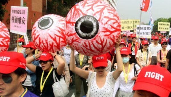 Những người tham gia phong trào công đoàn Đài Loan cầm trong tay mô hình con mắt nhân tạo tấy đỏ tượng trưng cho sự mệt mỏi của công nhân - Sputnik Việt Nam