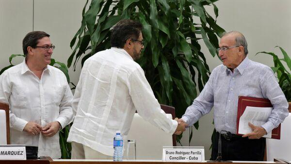 Представитель Революционных вооруженных сил Колумбии Иван Маркес и представитель правительства Колумбии Умберто де ла Калье на подписании соглашения в Гаване - Sputnik Việt Nam