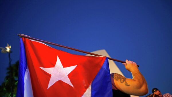 An anti-Castro Cuban exile holds a Cuban flag during a protest after the announcement of restoring diplomatic ties between Cuba and United States, at an area knows as 'Little Havana' in downtown Miami, Florida December 17, 2014. - Sputnik Việt Nam