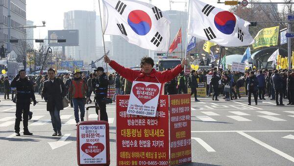 Мужчина держит национальные флаги Южной Кореи в поддержку президента Пак Кын Хе - Sputnik Việt Nam
