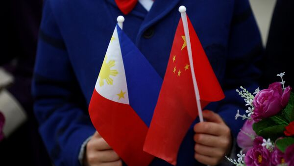 Children hold plastic flowers, national flags of China and the Philippines before President of the Philippines Rodrigo Duterte and China's President Xi Jinping attend a welcoming ceremony at the Great Hall of the People in Beijing, China, October 20, 2016 - Sputnik Việt Nam