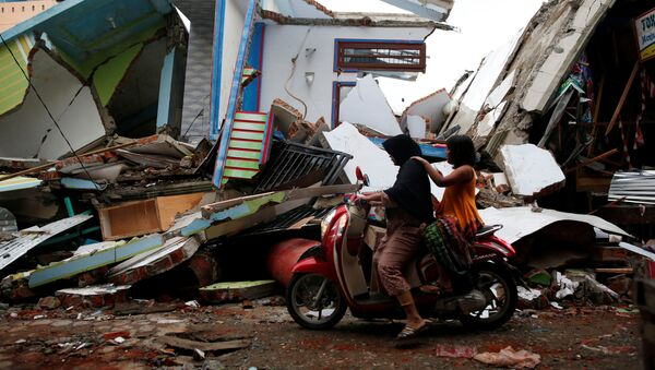 A woman and child ride a motorcycle past damaged buildings following this week's strong earthquake in Meureudu market, Pidie Jaya, Aceh province, Indonesia December 9, 2016. - Sputnik Việt Nam