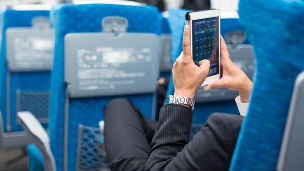 Бизнесмен с телефоном в руках в салоне самолета - Sputnik Việt Nam