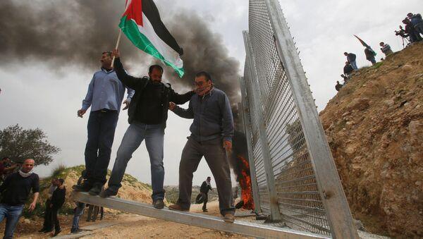Người Palestine phá hàng rào do người Israel dựng trong cuộc biểu tình phản đối tại thành phố ở Bờ Tây sông Jordan. - Sputnik Việt Nam