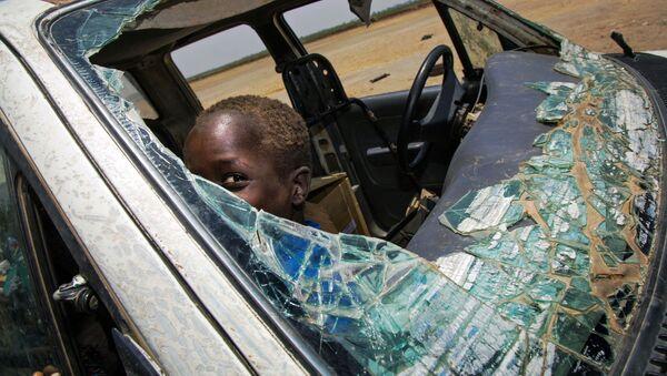 Nam Sudan. Đứa trẻ chơi đùa trong chiếc xe ô tô bị phá vỡ  vì chiến sự. - Sputnik Việt Nam
