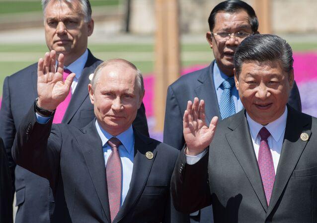 Президент РФ Владимир Путин и председатель КНР Си Цзиньпин на церемонии совместного фотографирования участников круглого стола Международного форума Один пояс, один путь