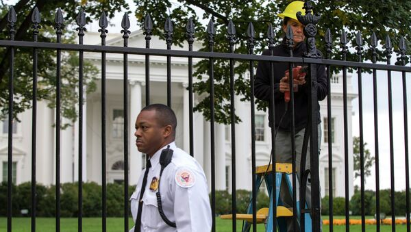A Secret Service police officer walks outside the White House in Washington, Thursday, Oct. 23, 2014, as a maintenance worker performs fence repairs as part of a previous fence restoration project. - Sputnik Việt Nam