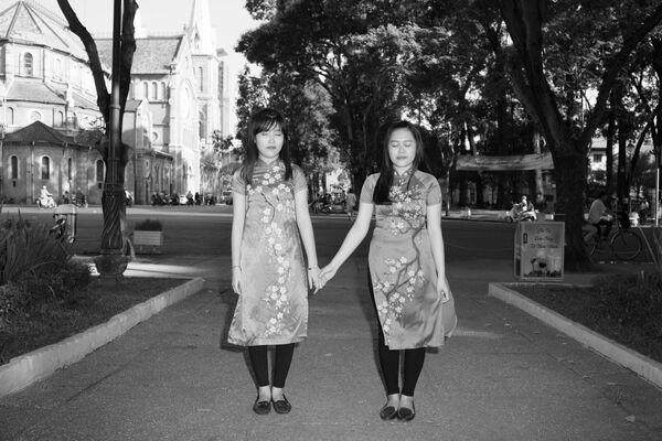 Hai chị em tạo dáng chụp hình trong trang phục truyền thống ở  một công viên Sài Gòn - Sputnik Việt Nam