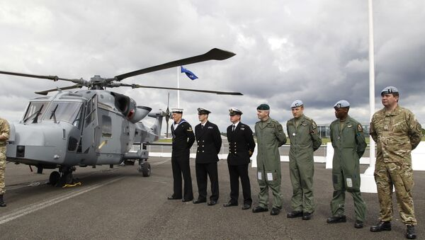 British forces' personnel stand to attention in front of a new AgustaWestland AW159 Wildcat helicopter at the Farnborough International Airshow in Farnborough, England (file) - Sputnik Việt Nam