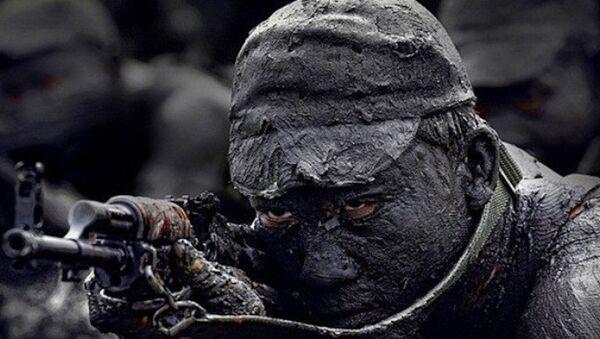 Chiến sĩ đặc công với kỹ thuật ngụy trang dùng bùn đất. Nguồn ảnh: Báo QĐND - Sputnik Việt Nam