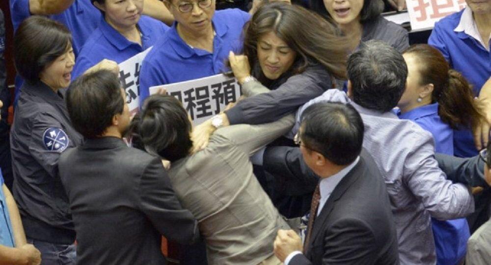 Nghị sĩ Hsu Shu-hua (áo đậm hơn, Quốc dân đảng) cố bóp cổ nghị sĩ Chu Yi-ying (đảng Dân tiến) trong khi các đồng nghiệp lao vào để ngăn cản người.
