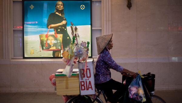 Người bán hàng rong đạp xe ngang qua trung tâm thương mại, Hà Nội, Việt Nam - Sputnik Việt Nam