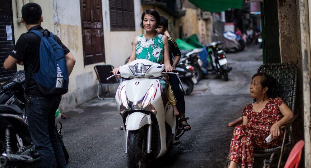 Cô gái đi xe máy trên một phố cổ Hà Nội