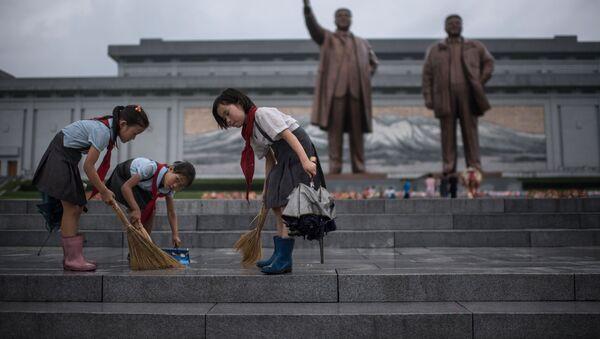 Bình Nhưỡng. Những đứa trẻ lau bậc cầu thang phía trước tượng đài lãnh tụ Kim Nhật Thành và Kim Chính Nhật. - Sputnik Việt Nam