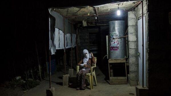 Souhayla ngồi bên ngoài túp lều của người chú ở Shariya, Iraq hôm 20/7. - Sputnik Việt Nam