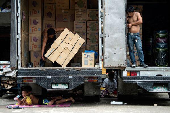 Manila. Những đứa trẻ Philippines tìm thấy bóng rợp...dưới một chiếc xe tải. - Sputnik Việt Nam