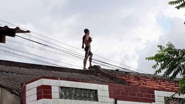 Nam thanh niên trèo lên nóc nhà dân - Sputnik Việt Nam