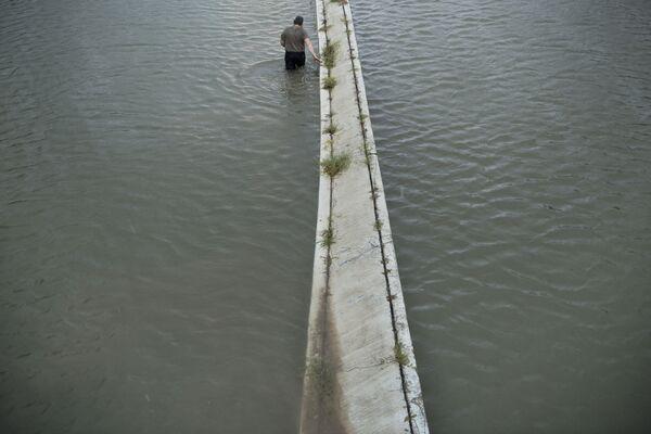 Người lái xe tải kiểm tra mực nước lụt trên đường cho xe chạy... - Sputnik Việt Nam