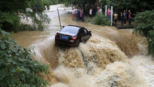 Chiếc ô tô mắc kẹt giữa lũ lụt sông tràn  bờ ở Trùng Khánh, Trung Quốc - Sputnik Việt Nam