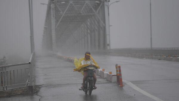 """Cô gái Việt chạy xe trên con đường trống rỗng trong cơn bão """"Doksuri"""". - Sputnik Việt Nam"""