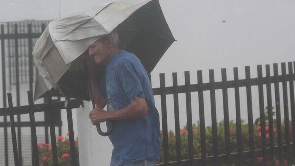 Мужчина с зонтом на улице во время урагана Ирма в Пуэрто-Рико - Sputnik Việt Nam