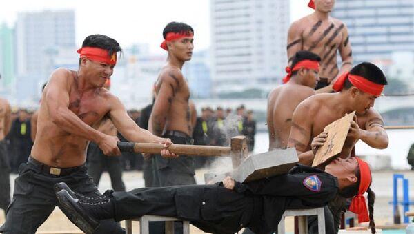 Màn biểu diễn để các đồng nghiệp nam dùng búa tạ đập vỡ đá tảng kê trên bụng của nữ chiến sĩ K20 - Sputnik Việt Nam